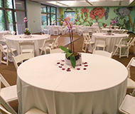 gorgeous indoor settings overlook the forest white chairs and aisle runner provided this venue accommodates up to 150 people
